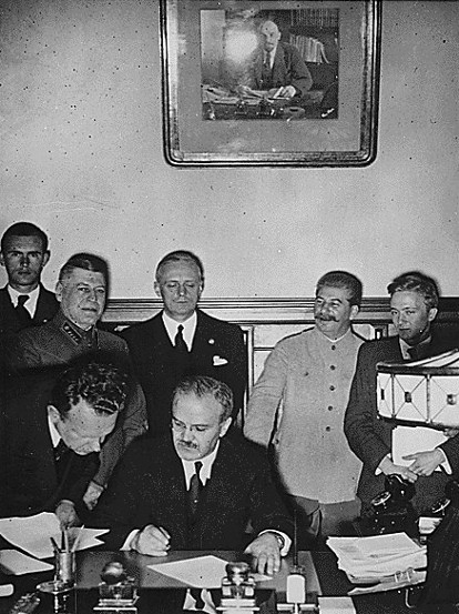 Image - Viacheslav Molotov signs the German-Soviet non-aggression pact (Ribbentrop and Stalin in the background).